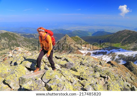 Woman hiker during a mountain trip in sunny day - stock photo