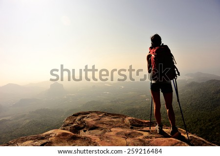 woman hiker enjoy the view at sunset mountain peak cliff