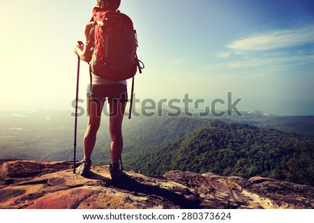 woman hiker enjoy the view at sunset mountain peak cliff - stock photo