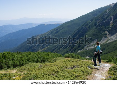 Woman hiker enjoying the view in the mountains - stock photo