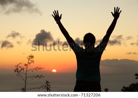 Woman hiker in silhouette standing arms raised to sunset