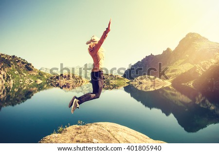 Woman hiker jumping up Flying levitation with lake and mountains on background Lifestyle Travel emotions concept outdoor  - stock photo