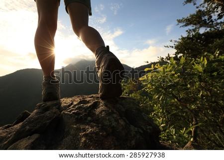 woman hiker legs climbing on sunrise mountain peak rock - stock photo