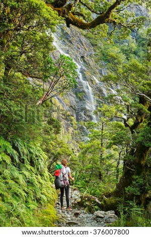 woman hiker looking at Earland Falls on Routeburn Track in New Zealand - stock photo