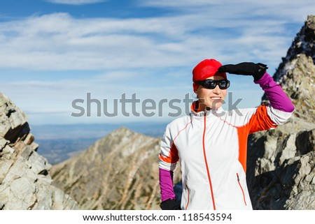 Woman hiker looking at mountain view in Tatra Mountains. Beauty female trail runner looking at sunset in sunglasses. Recreation and healthy lifestyle outdoors in nature, Poland