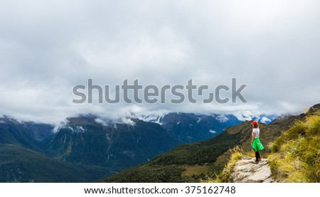 Woman hiker looking at the view of Routeburn Track in South Island, New Zealand