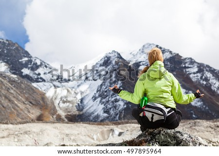 Woman Hiker Meditating on Rocks in Himalaya Mountains, Nepal. Young Girl Looking at Beautiful Inspirational Landscape. Recreation Meditating Outdoors in High Mountains in Nepal.
