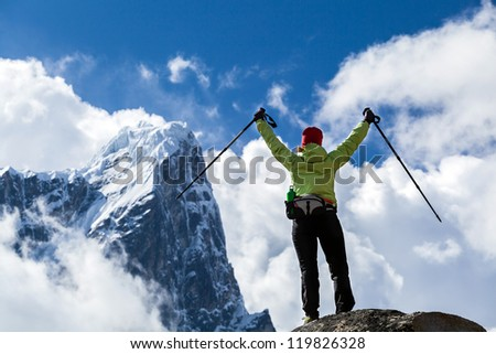 Woman hiker nordic walking and success in mountains, arms outstretched. Trekking, climbing in autumn nature, beautiful Himalaya Mountain landscape, Nepal.