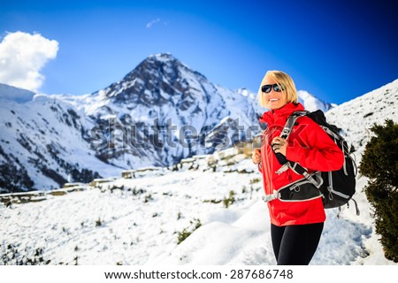 Woman hiker nordic walking, healthy lifestyle in Himalaya Mountains in Nepal. Trekking and hiking on snow white winter nature, beautiful inspirational mountain landscape. - stock photo