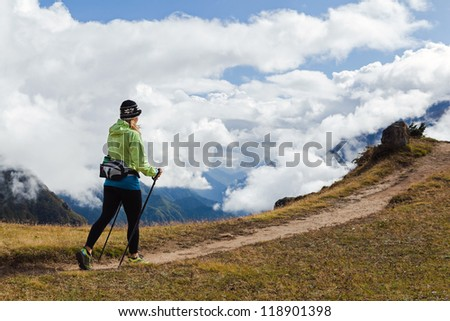 Woman hiker nordic walking in Himalaya Mountains in Nepal. Trekking in autumn nature, beautiful mountain landscape. Sport and exercising - stock photo