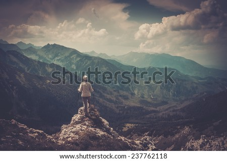 Woman hiker on a top of a mountain  - stock photo