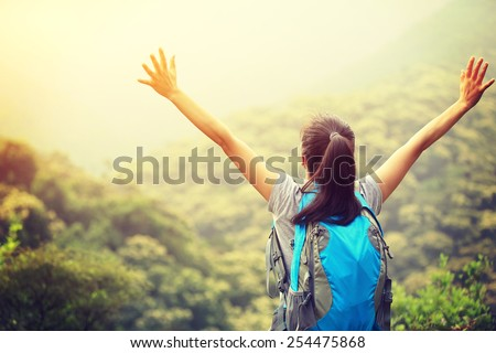 woman hiker open arms to mountains - stock photo