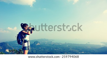 woman hiker photographer taking photo at mountain peak   - stock photo