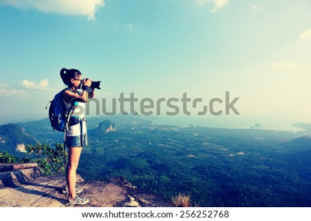 woman hiker photographer taking photo at mountain peak cliff - stock photo
