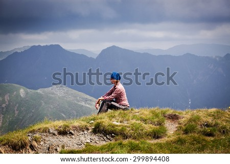 Woman hiker relaxing on a top of a mountain