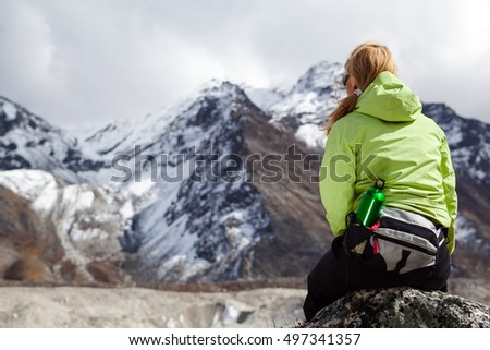Woman hiker relaxing on rocks in Himalaya Mountains, Nepal. Young Girl Looking at Beautiful Inspirational Landscape. Recreation Meditating Outdoors in High Mountains in Nepal.