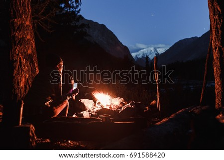 Woman hiker sits near the bonfire in the camp and admires the mountains under the starry sky