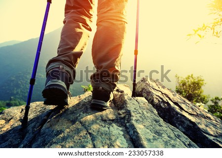 woman hiker stand on mountain peak rock enjoy the view - stock photo