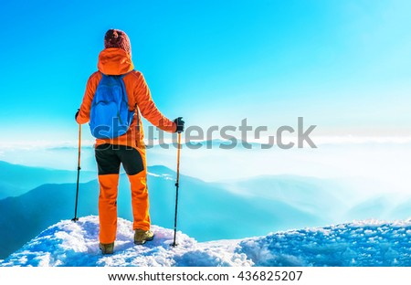 Woman hiker successful on mountain peak summit in winter mountains. Active sport concept.