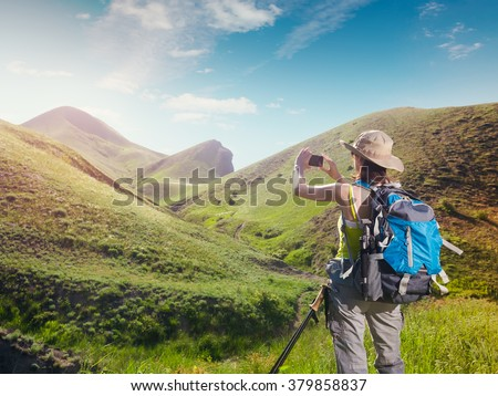 Woman hiker taking photo with smartphone at mountain nature. Backpacker photographs on a mobile phone.