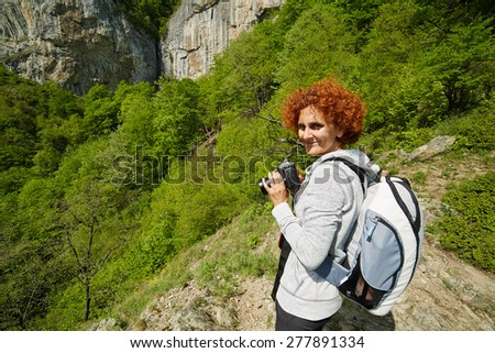 Woman hiker taking photos of a beautiful waterfall on a mountain trail - stock photo