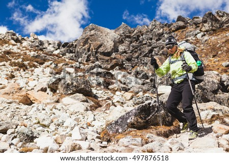 Woman hiker trekking with big backpack in Himalaya Mountains on Rocky Trail. Girl on hiking trail in high mountains, travel and expedition in inspirational mountain landscape with beautiful views.
