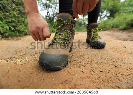woman hiker tying shoelace on forest trail