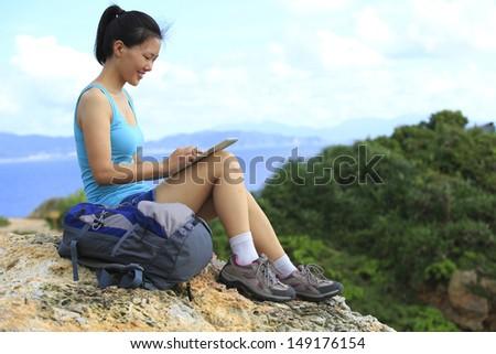 woman hiker use tablet pc sit on seaside mountain peak rock - stock photo