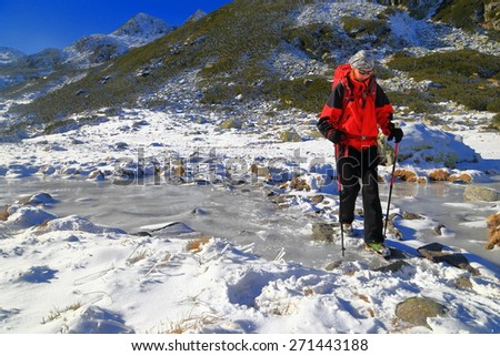 Woman hiker walking across icy river - stock photo