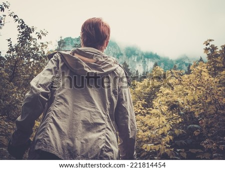 Woman hiker walking in mountain landscape  - stock photo