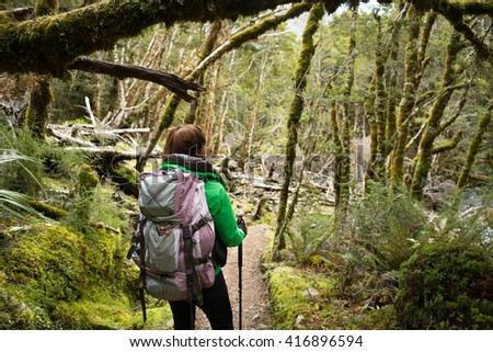 Woman hiker walking in the forest on Kepler Track, New Zealand - stock photo