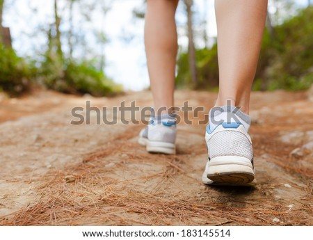 Woman hiker walking on the rural road. Traveling concept. - stock photo