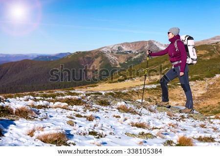 Woman Hiker walking up on snowy Winter Mountain Slope with Backpack and trekking Poles watching further Way to Summit Sun Shining from Clear Blue Sky - stock photo
