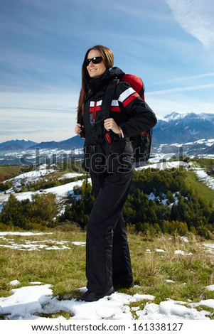 Woman hiker with backpack enjoying a hiking trip in the mountains