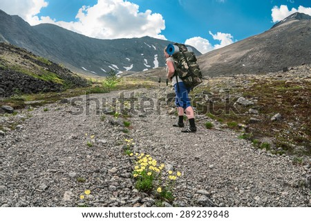 Woman hiker with backpack follows the main group climbing the mountain road - stock photo