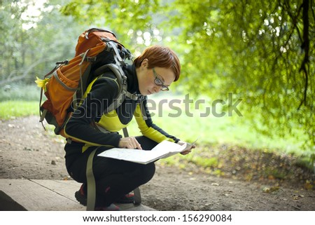Woman hiker with backpack holding a map in the countryside - stock photo