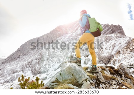 Woman hiker with backpack on top of mountain stopped on sunny mountain ledge to catch breath after long hike - stock photo
