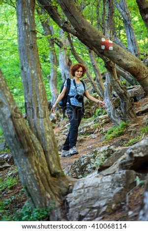 Woman hiker with backpack trekking into the woods on a mountain trail