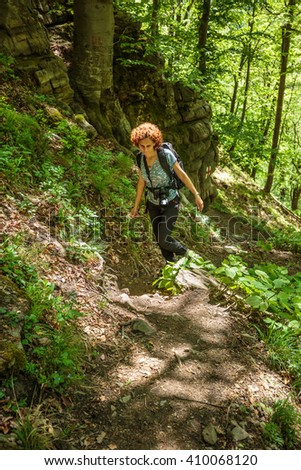Woman hiker with backpack trekking into the woods on a mountain trail - stock photo