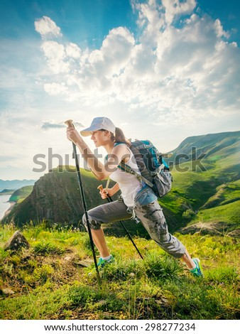 Woman hikers climbs a mountain on the grass track. Hiking. Backpacker girl. - stock photo