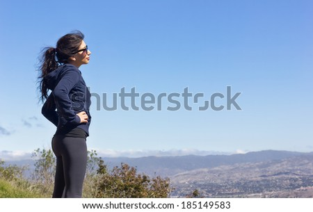Woman hikes to the top of the mountain.