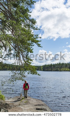 Woman hiking and looking lake landscape with dog on high cliff in nature park in Finland