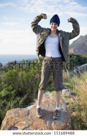 Woman hiking and showing her strength looking at camera in the countryside - stock photo