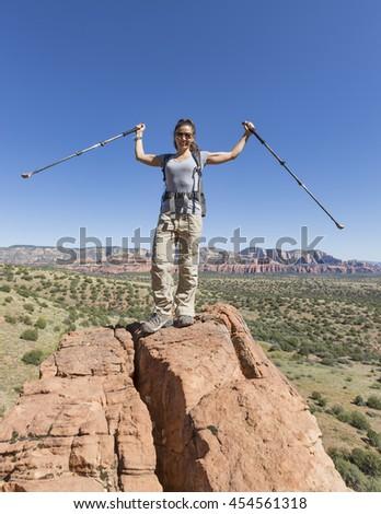 Woman hiking celebrates after reaching pinnacle - stock photo