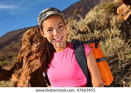 Woman hiking closeup. Young asian female model hiking / backpacking in beautiful volcanic landscape on the volcano, Teide, Tenerife, Spain. - stock photo
