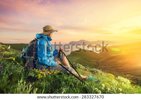 Woman hiking. Hiker with backpack relaxing on grass and enjoying sunset. Hike in the mountains. - stock photo