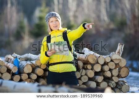 Woman hiking in forest reading map. Recreation and healthy lifestyle outdoors in nature. Beauty blond looking at camera on sunset. - stock photo