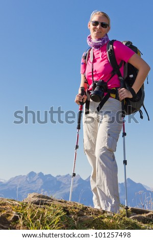 woman hiking in high mountains with sunglasses walking sticks, backpack and camera, Switzerland - stock photo