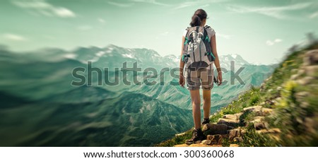 Woman hiking in mountain range. Rear view of a female backpacker walking on a small foot path in a mountain landscape. Image for trekking, hiking or climbing. - stock photo