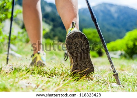 Woman hiking in mountains, adventure and exercising. Nordic walking in sunny  summer nature outdoors. Legs and sport shoes walk on grass - stock photo
